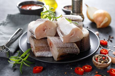 Raw fresh sliced hake fish with ingredients for cooking