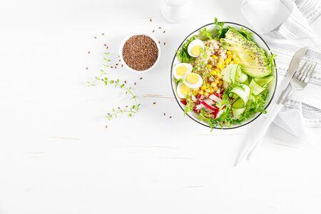 Breakfast oatmeal porridge with fresh vegetable salad of cucumber, radish, lettuce, corn, avocado, chia seeds and boiled eggs. Healthy balanced food. Top view. Flat lay Banco de Imagens