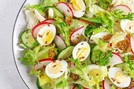 Fresh vegetable salad with cucumber, radish, lettuce and boiled eggs. Helathy food. Top view. Flat lay