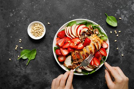 Grilled chicken breast and strawberry salad with red apples, fresh spinach and nuts Foto de archivo