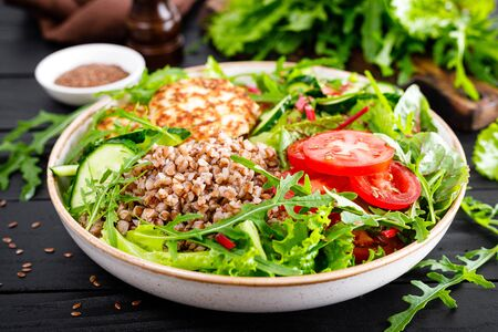 Lunch bowl with buckwheat porridge, fried chicken cutlets and fresh vegetable salad of arugula, lettuce, chard leaves, tomato, cucumber and flax seeds