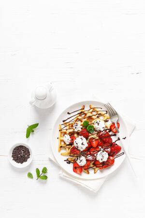Belgian waffles with fresh strawberry, chocolate topping and whipped cream