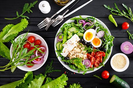 Greek style healthy breakfast bowl with oatmeal porridge and fresh vegetable salad of lettuce, arugula, olives, tomato, cucumber, feta cheese and boiled egg