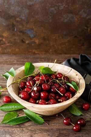 Sweet cherry with leaves in wooden bowl. Fresh ripe cherries. Cherry fruit Stockfoto
