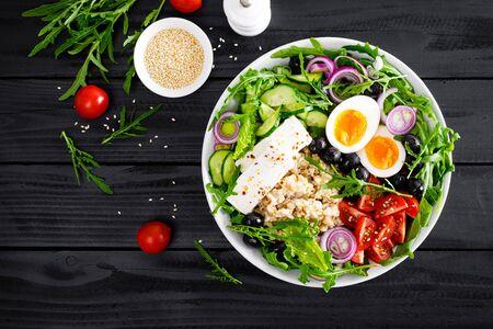 Greek style healthy breakfast bowl with oatmeal porridge and fresh vegetable salad of lettuce, arugula, olives, tomato, cucumber, feta cheese and boiled egg