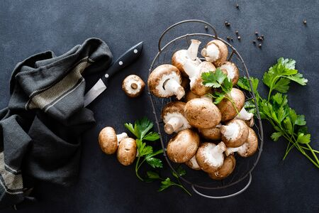 Raw mushrooms champignons on black background, cooking fresh champignons
