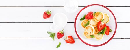 Cheese pancakes, fritters or syrniki with fresh strawberry and yogurt. Healthy and tasty breakfast. Banner