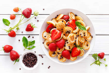 Mini pancakes with fresh strawberry and chocolate drops
