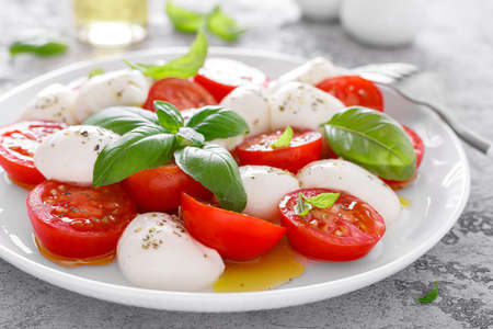 Caprese salad. Salad with mozzarella cheese fresh tomatoes, basil leaves and olive oil. Italian food