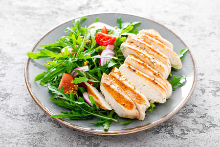 Chicken fillet salad with fresh vegetables and arugula. Fresh vegetable salad of arugula, tomatoes, onion and grilled chicken breast. Stockfoto