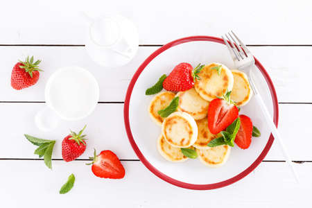 Cheese pancakes, fritters or syrniki with fresh strawberry and yogurt. Healthy and tasty breakfast Stockfoto