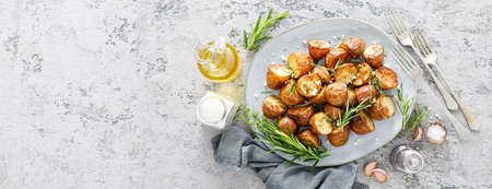 Baked potatoes with rosemary, thyme and garlic. Banner
