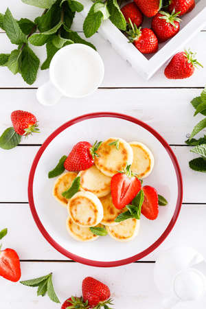 Cheese pancakes, fritters or syrniki with fresh strawberry and yogurt. Healthy and tasty breakfast 版權商用圖片