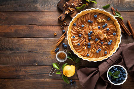 Thanksgiving pear tart, pie or cake with fresh pears and blueberry, cinnamon and walnuts