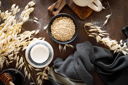 Vegan oat milk in glass bottle and ingredients for cooking. Healthy vegetarian non-dairy drink or beverage. Alternative milk 版權商用圖片