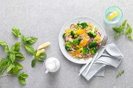 Vegan quinoa and broccoli warm salad with oranges and fresh onion, top down view