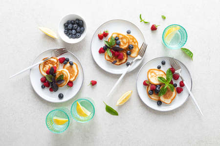 Pancakes with fresh blueberry and raspberry served for healthy vegetarian breakfast