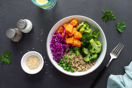 Vegetarian quinoa and broccoli lunch Buddha bowl with baked butternut squash or pumpkin, green peas and red cabbage, top down view
