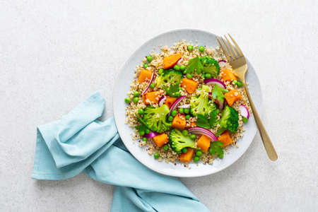 Vegetarian quinoa and broccoli warm salad with baked butternut squash or pumpkin, green peas and fresh red onion, top down view