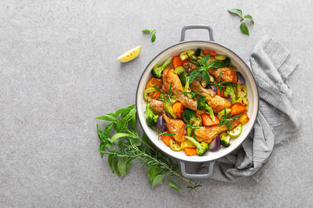Chicken drumsticks roasted with vegetables in cast iron pan on kitchen table, top down view 版權商用圖片