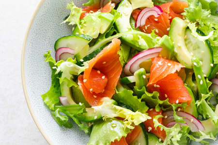 Salmon avocado salad with salted fish, lettuce, red onion and cucumbers