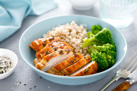 Baked chicken lunch bowl with pearl barley and broccoli