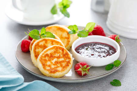 Cottage cheese pancakes, sweet curd fritters with berries, syrniki with jam and fresh raspberry on breakfast table