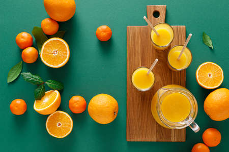 Freshly squeezed orange juice in a glass pitcher and fresh fruits with leaves, healthy drink, vitamin c concept, top view