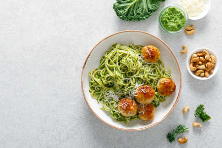 Chicken meatballs with pasta and green kale cashew pesto sauce, top view
