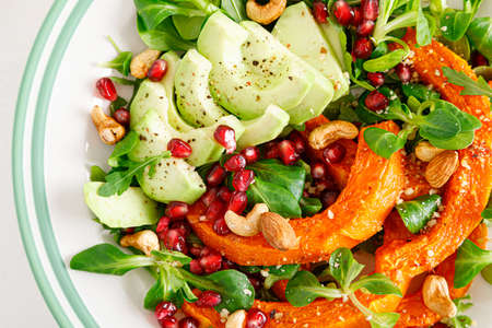 Fresh vegetable salad with lambs lettuce, baked butternut squash or pumpkin, avocado, pomegranate, cashew and almond nuts. Healthy vegetarian food concept. Top view Stok Fotoğraf