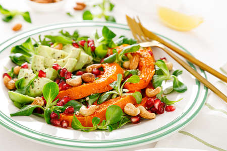 Fresh vegetable salad with lambs lettuce, baked butternut squash or pumpkin, avocado, pomegranate, cashew and almond nuts. Healthy vegetarian food concept. Stok Fotoğraf