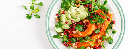 Fresh vegetable salad with lambs lettuce, baked butternut squash or pumpkin, avocado, pomegranate, cashew and almond nuts. Healthy vegetarian food concept. Top view. Banner