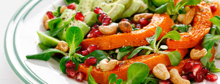 Fresh vegetable salad with lambs lettuce, baked butternut squash or pumpkin, avocado, pomegranate, cashew and almond nuts. Healthy vegetarian food concept. Banner