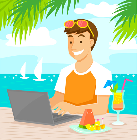 Young man working on his laptop at the beach while enjoying tropical fruit and a cocktail.