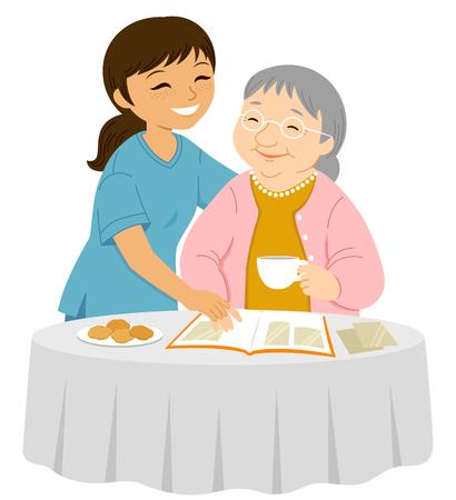 Junge Pflegerin lächelt einer älteren Frau zu, die Fotos in ein Album legt