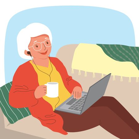 Senior woman using a laptop with earphones while relaxing on the sofa.