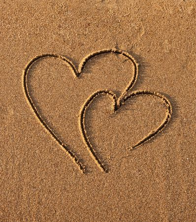 Two connected hearts drawn on wet sand photo