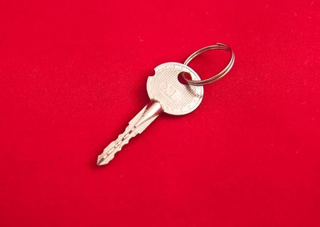 Small silver key on a red background Stock Photo - 6204777