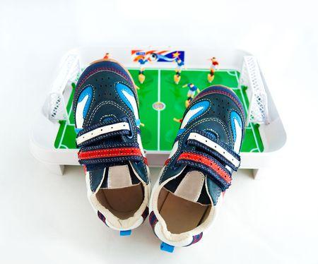 futbol infantil: Calzado de deporte de la infancia contra un terreno de f�tbol de juguete  Foto de archivo