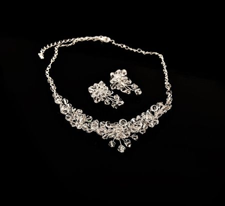 diamond shaped: Diamond necklace and earrings on a black background