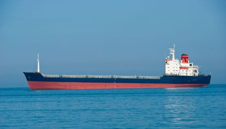 The industrial vessel - the dry-cargo ship goes to port photo
