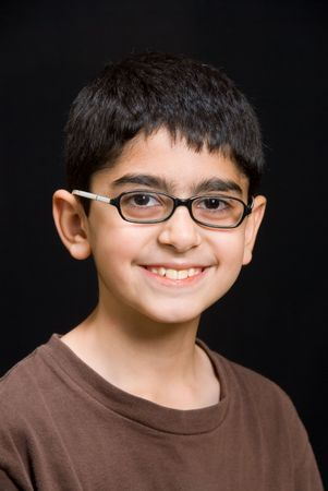 A portrait of an Indian boy against a black background