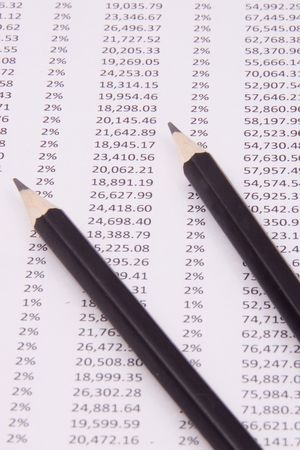 tabulation: A computer data table showing lots of numbers; with two pencils on top Stock Photo