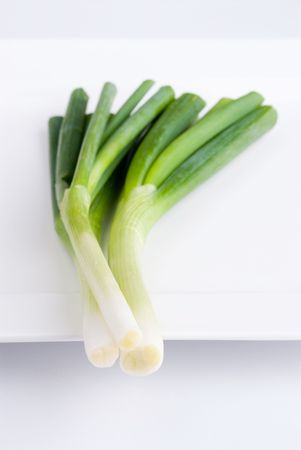 A bunch of fresh spring onions on a white plate. Shallow depth of field.