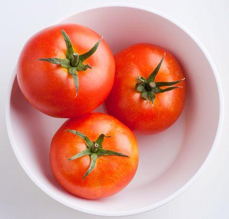 Three ripe tomatoes in a white bowl - top view Banco de Imagens