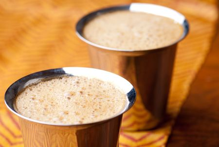 frothy: Frothy South Indian coffee served in steel glasses Stock Photo