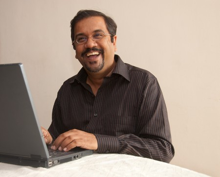 A smiling Indian man working on his laptop