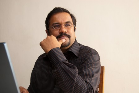 An Indian man thinking while sitting in front of his laptop Stock Photo