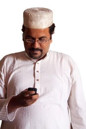 Muslim man checks his mobile phone - isolated on white Banco de Imagens