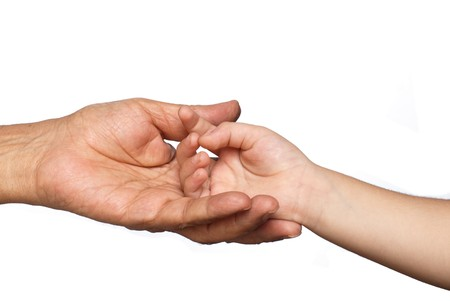 hold: A senior persons hand cradling a young boys hand